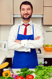 Man in blue apron with folded hands Royalty Free Stock Image