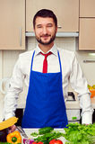 Man in blue apron in the kitchen Stock Image