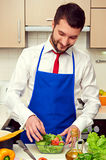 Man in blue apron preparing fresh salad Stock Images