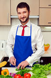 Man in blue apron preparing in the kitchen Stock Photos