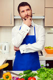 Man in blue apron thinking and looking up Royalty Free Stock Image
