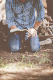 Man in Blue and Black Flannel and Blue Jeans Holding Book Kneeling on Brown Ground Royalty Free Stock Images