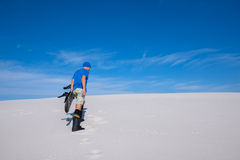 Man in blue cap with a snowboard climbs up the sand dune Stock Image