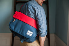 Man in Blue Chambray Long Sleeve Shirt With Red and Blue Herschel Sling Bag Royalty Free Stock Photos