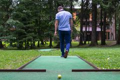 man in blue clothes goes to the place of impact for playing mini-golf royalty free stock photography
