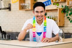 Man with blue cocktail. Portrait of a bartender stirring blue cocktail in bar royalty free stock photography