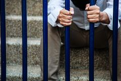 A man in blue collar shirt and black slacks behind the iron fence, Hand holding iron fence with a sense of hopelessness, sadness. Solitude, sorrow, melancholy Royalty Free Stock Images