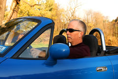 Man in a Blue Convertible. Middle-aged man driving a blue convertible - sign of a mid-life crisis Royalty Free Stock Image