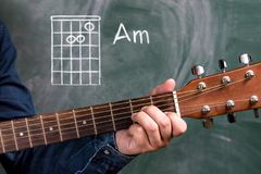 Man playing guitar chords displayed on a blackboard, Chord Am Stock Image