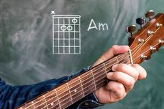 Man playing guitar chords displayed on a blackboard, Chord A minor. Man in a blue denim shirt playing guitar chords displayed on a blackboard, Chord A minor Royalty Free Stock Image