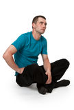 Man in a blue dress sitting. In a lotus position on a white floor Stock Photography