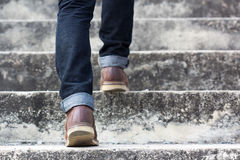 A man with blue geans and  sneaker shoes in stair Stock Photos