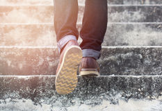 A man with blue geans and sneaker shoes in stair stock image
