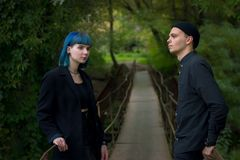 Man and blue hair girl at black clothes at green river background Stock Photo
