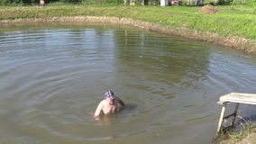 Man with blue hat swim to shore in rural pond stock footage
