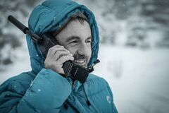Man in Blue Hoodie Jacket Holding Black Radio Receiver during Snowy Day Time Stock Images