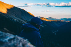 Man in Blue Hoodie Standing on Mountain Cliff during Daytime Royalty Free Stock Photos