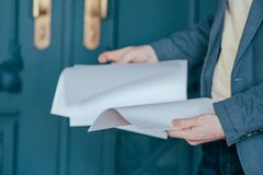 The man in blue jacket suit holding sheets of paper in hands, close up stock image