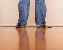 Man in blue jean walking. On wooden floor Stock Photos