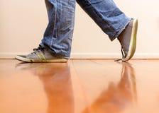 Man in blue jean walking. On wooden floor Royalty Free Stock Image