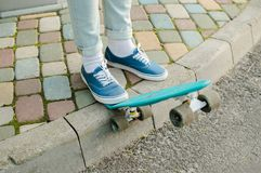 Penny skateboard commute hipster transport solutions. Man in blue jeans and canvas shoes stading with blue plastic penny scateboard on the pavement . Concept of Royalty Free Stock Images
