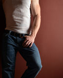 Man in blue jeans. Lower body shot of a muscular man in a wife beater and blue jeans stock photo