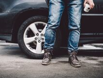 Man in blue jeans next to car Royalty Free Stock Images