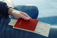 Man in blue jeans sits and holds in his hand passport of red color with tickets to plane. Сlose up. Top view Stock Photos