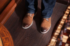 Man in blue jeans and yellow boots. Standing on a dark floor Stock Images