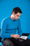 Man in a blue jersey with a notebook Stock Image