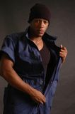 Man in a blue jump suit. African american male in blue jump suit and hat royalty free stock images