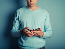Man in blue jumper using smart phone Stock Images