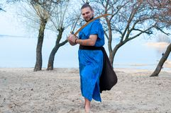 Man in blue kimono, bun and sticks on head training with sword and looking away stock image