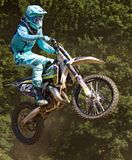 Man in Blue Mtx Suit Riding Blue and Yellow Dirt Motorcycle in Air Stock Images