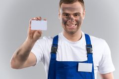 Man in blue overalls holding business card. Stock Photography