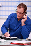Man in blue overalls speaking. On telephone Royalty Free Stock Photo
