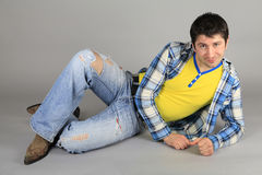 Man in a blue, plaid shirt and torn jeans Stock Photography