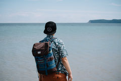Man in Blue Shirt Carrying a Backpack Standing Near Sea Stock Image