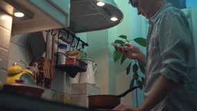 Man cooking meal in pot on stove in kitchen, using smartphone. Man in blue shirt cooking meal in red pot on stove in kitchen. using smartphone stock video footage