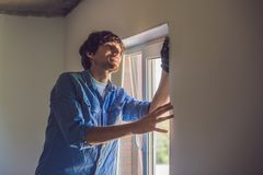 Man in a blue shirt does window installation.  stock photos