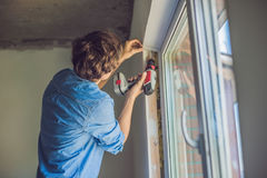 Man in a blue shirt does window installation.  Stock Images