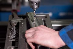 A man in a blue shirt drills a hole in the details at a small enterprise.  Stock Photography
