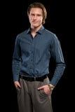 Man in Blue Shirt and Grey Slacks. Studio shot over black Royalty Free Stock Photos