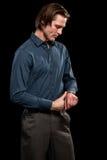 Man in Blue Shirt and Grey Slacks. Studio shot over black Royalty Free Stock Image