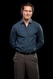 Man in Blue Shirt and Grey Slacks. Studio shot over black Stock Photography