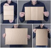 A man holding booklet. A man in a blue shirt holding a blank booklet, notebook royalty free stock photo
