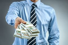 Man in blue shirt holding cash of one hundred dollars Stock Image