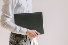 A man in a blue shirt holds a folder stock photos