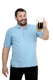Bearded chap inviting to beer fest. Jolly bearded chap in blue polo shirt inviting to beer festival holds two tankards in left hand Stock Image