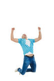 Man in blue shirt and jeans jumping in the air with his hands ra Stock Photos